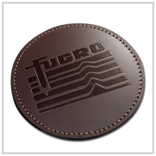brown round leather coaster with dark brown deboss imprint