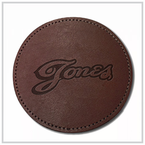 black round leather coaster with red deboss imprint